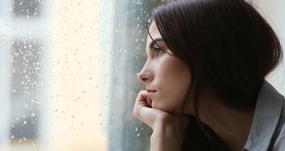 雨の外を見る女